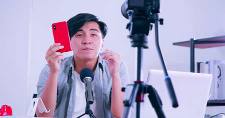 Young asian man selling digital gadgets on social media by streaming live from his home.