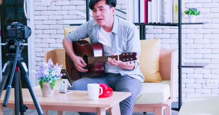 A young Asian man is playing the guitar and singing on social media by streaming live from his home. Foto de archivo