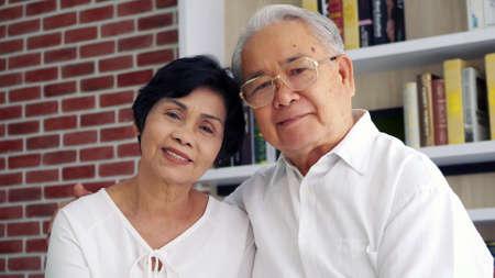 Portrait of happy Asian elderly couple sitting on sofa. Foto de archivo