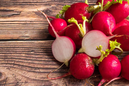 Top view of sliced red ripe radishes on wooden background