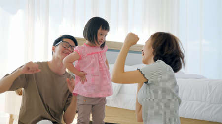Happy family with mother, father and disabled daughter having fun dancing together at home.