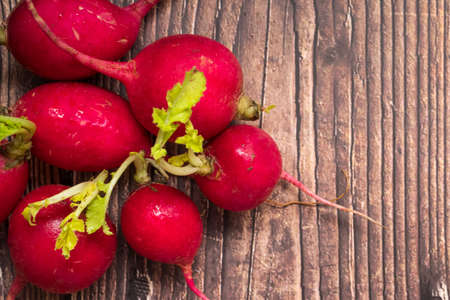 Top view of red ripe radishes on wooden background