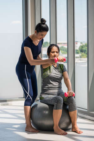 Two asian women doing yoga together at a gym. Foto de archivo