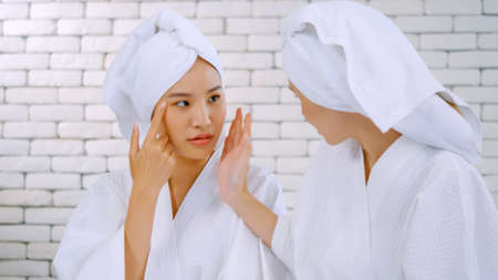 Two Asian girls in white bathrobes with towels on heads talking in living room.
