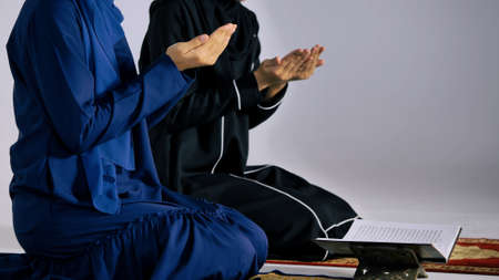 Two Asian Muslim young women in traditional hijab are praying glorify Allah and practicing the Islamic faith in mosque.