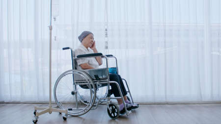 An elderly woman with cancer sits in a wheelchair and she has a headache while being hospitalized.