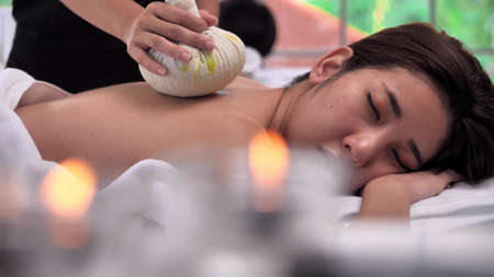 Young Asian woman getting relaxing during therapist put herbal spa ball on the back and massage in spa salon.