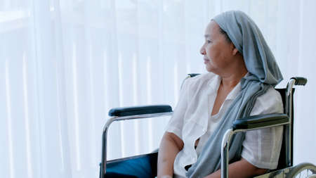 An elderly woman with cancer sitting in a wheelchair looking out of the window while being hospitalized.