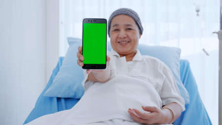 An elderly woman with cancer sitting on bed and showing some information on her smart phone.