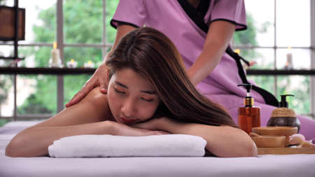 The massage therapist massaging on the back of young Asian woman with aroma essential oil skincare at spa salon.