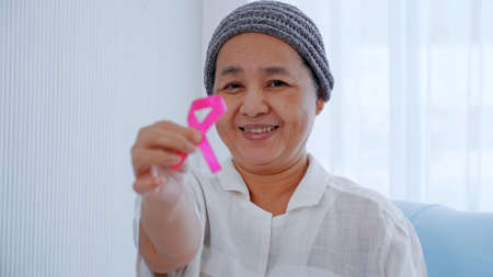 Elderly female patient holding pink ribbon in hospital. Breast cancer awareness concept.