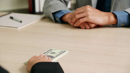 Businessman take bribes from entrepreneur, they agree to do business together.
