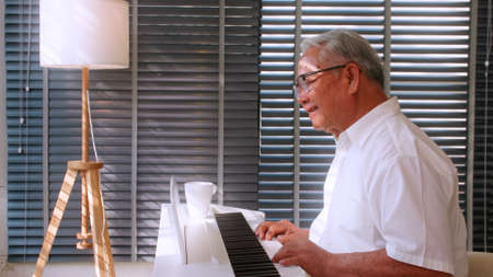 An elderly Asian man practicing playing the piano in the living room of his home after retirement from work. Stock fotó