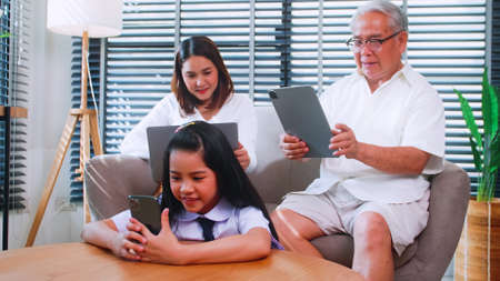 Grandpa, mother and daughter use wireless technology while relaxing in the living room. Asian family is enjoying the modern mobile technology in their home.