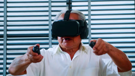 Asian senior man having fun playing video game with virtual reality glasses at home.