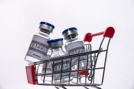 Glass vials for vaccine in shopping cart on white background. Group of vaccine bottles in basket.