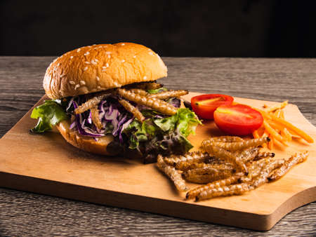 Burger with fried bamboo caterpillar and vegetable salad on wooden plate.