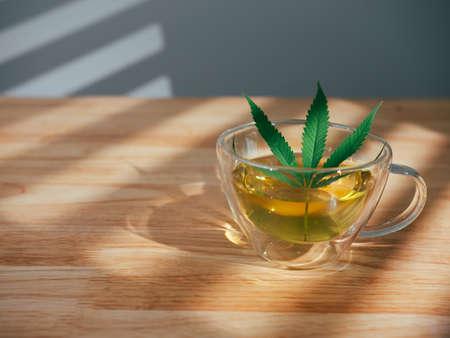 A glass of hot marijuana tea on the wooden table. Cannabis herbal tea with green leaf.