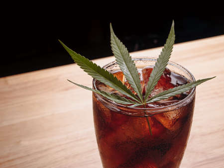 Glass of cola with ice cubes and cannabis leaf on the wooden table.