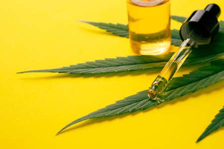 Cannabis oil in the dropper tube with green leaf on yellow background. Alternative medicine concept. Archivio Fotografico