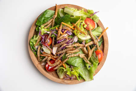 Vegetable salad with fried bamboo caterpillar in a wooden bowl.