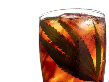 Glass of cola with ice cubes and cannabis leaf on white background. Archivio Fotografico