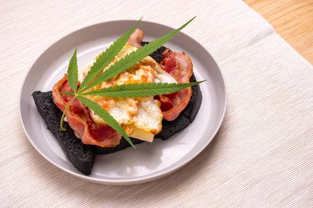 Homemade breakfast with marijuana or cannabis leaf on white plate.
