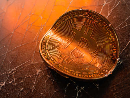 Twisted gold coin with bitcoin symbol. Concept of a cryptocurrency market crisis.