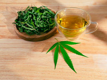 A glass of hot marijuana tea on the wooden table. Cannabis herbal tea with dried leaves.