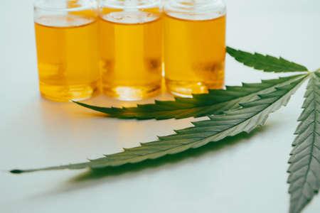 Cannabis oil in the vials with a green leaf on white background. Alternative medicine concept. Archivio Fotografico