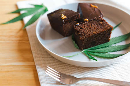 Homemade sweetmeat with marijuana or cannabis leaf on white plate. Alternative medicine concept.