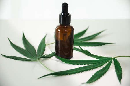 Cannabis oil in the dropper bottle with green leaves. Alternative medicine concept. Archivio Fotografico