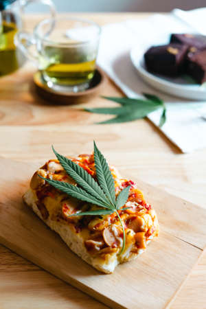 Homemade pizza with marijuana or cannabis leaf on wooden tray. Archivio Fotografico