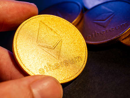 Hand holding golden coin with ethereum symbol.  Digital currency concept. Archivio Fotografico