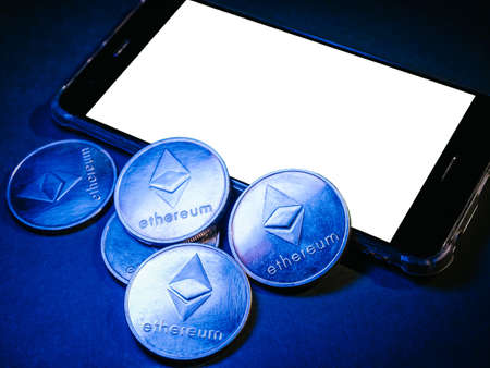 Smart phone with white screen and ethereum coins. Digital currency concept. Archivio Fotografico