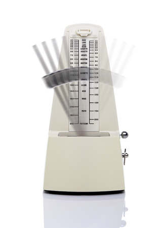 metronome: Fast-swinging metronome in action isolated on white background Stock Photo