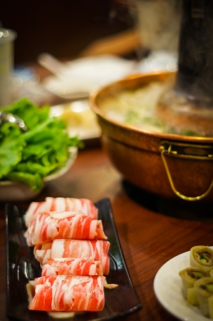 전통적인 뜨거운 석탄, 배경에 김이 냄비에 고기와 필드의 얕은 깊이에 초점을 아시아 스타일 쇠고기 양고기 전골