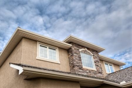 eaves: Roofline showing windows, brick stones, gutter, soffit, stucco