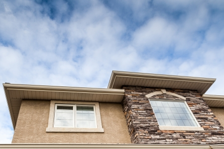 Roofline showing windows, brick stones, gutter, soffit, stucco