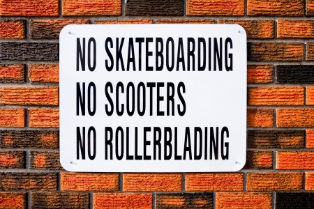 No skateboarding, no scooters, no rollerblading sign on red brick wall Stock Photo