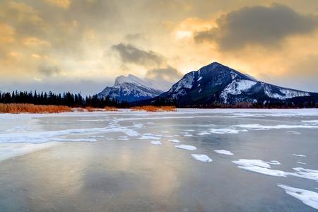마운트 런들 밴프 국립 공원에서 얼어 붙은 주홍 호수 위에 일출 스톡 콘텐츠