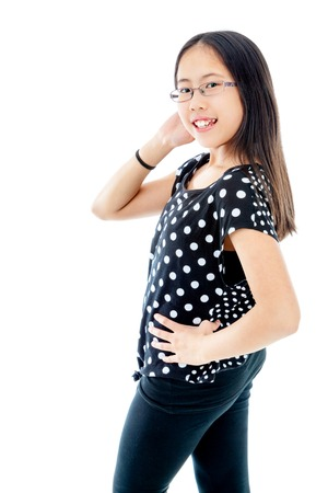 Asian tween girl striking a confident pose, isolated on white background