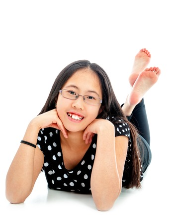 13 14 years: Asian tween girl lying on floor in confident pose, isolated on white background