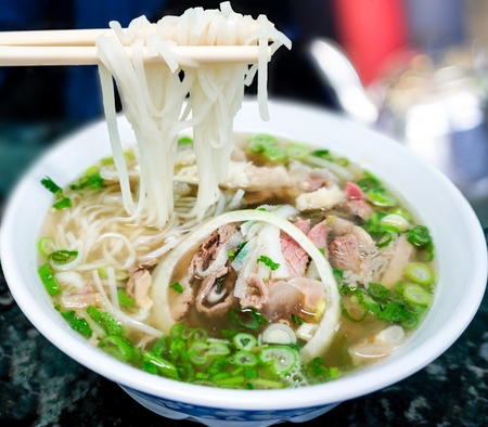Bowl of Vietnamese pho noodle soup with rare beef, tendon, tripe and brisket served with onions, scallions and cilantro  Stock Photo