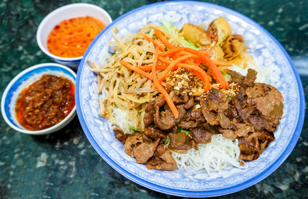 charbroiled: Traditional bowl of Vietnamese bun vermicelli rice stick noodle salad with charbroiled meat, shredded pork, deep fried spring rolls and pickled carrots served with mint leaves, peanuts and fish sauce   Stock Photo