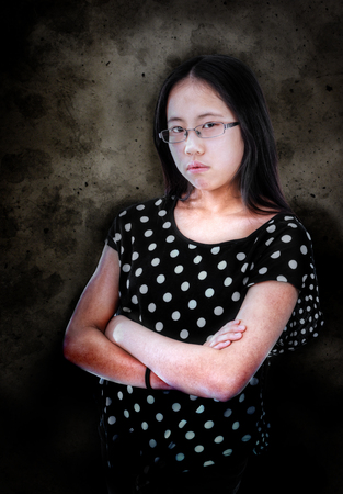 pre adolescence: Young girl with folded arms in a bad mood Stock Photo