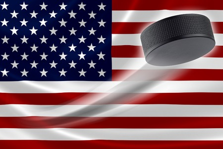 red america: Hockey puck streaks across the flag of United States, where the country is one of the worlds major ice hockey nations. Stock Photo