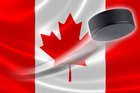 ice hockey puck: Hockey puck streaks across the flag of Canada, where the country is one of the worlds major ice hockey nations. Stock Photo