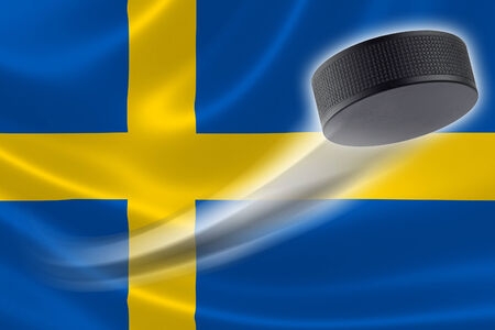 sweden flag: Hockey puck streaks across the flag of Sweden, where the country is one of the worlds major ice hockey nations. Stock Photo