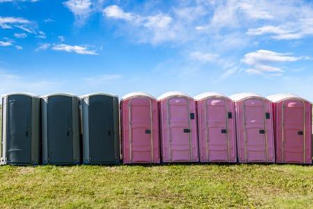グレーとピンク色プラスチック ポータブルトイレ屋外イベントのためのオープン フィールドに 写真素材